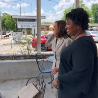 Not Presidential: Kamala Harris Posts Photo of Her and Stacey Abrams Laughing While Man is Passed Out or Dead on Bench in Background